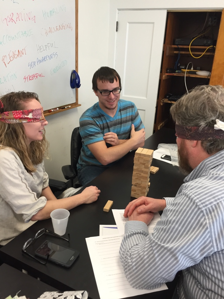 Training participants attempt to play Jenga blindfolded