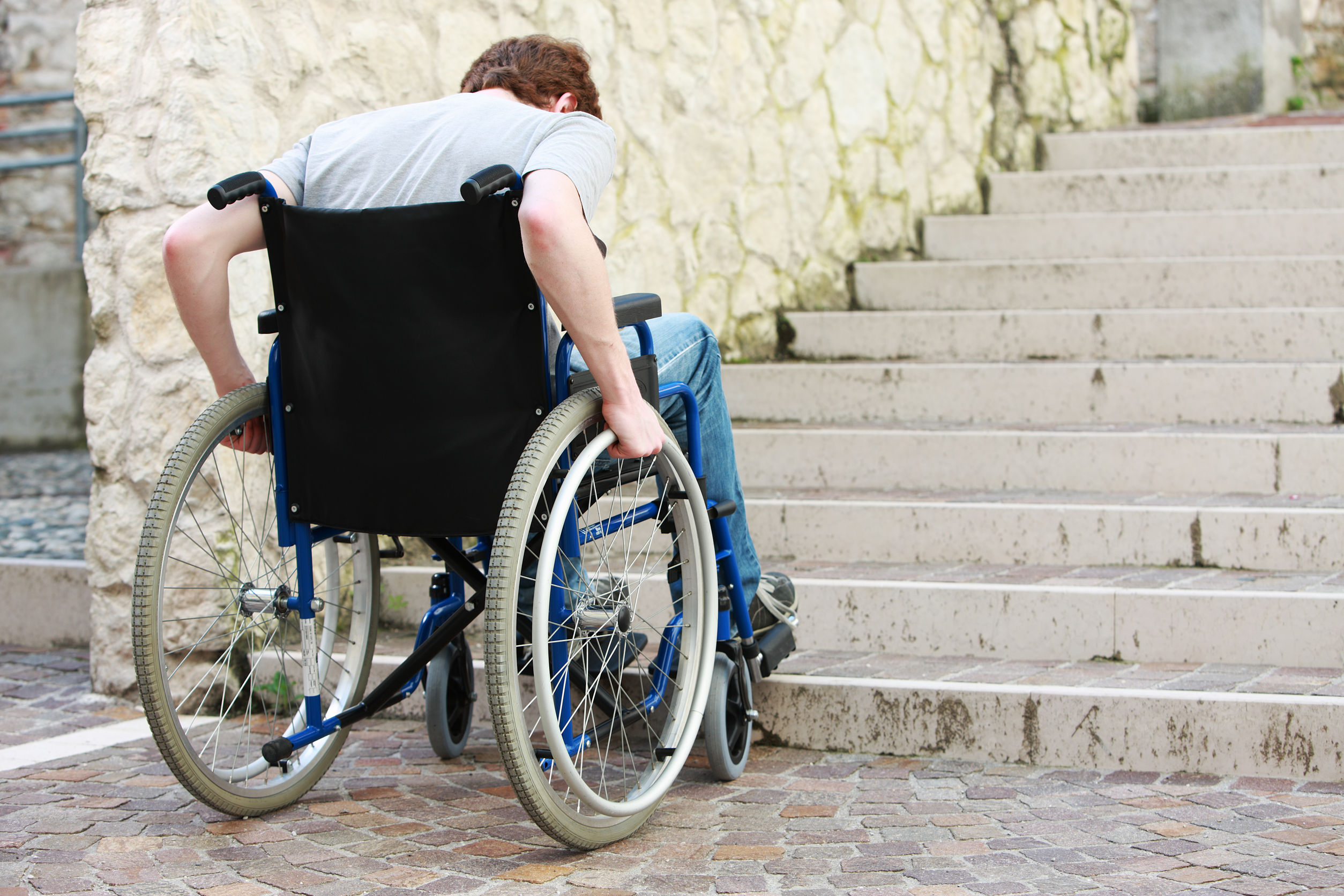 Man using wheelchair is blocked entrance due to stairs
