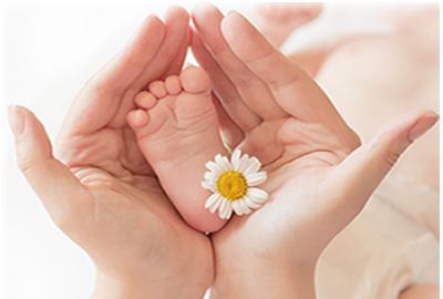Baby's foot being held in massage therapist's hands