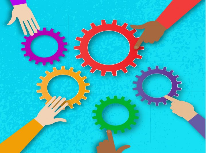 hands reaching to move gears in a puzzle
