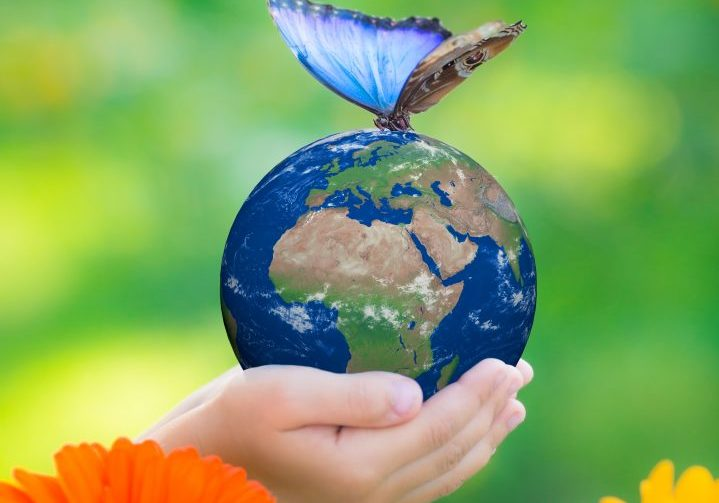 Child holding Earth planet with blue butterfly in hands against green spring